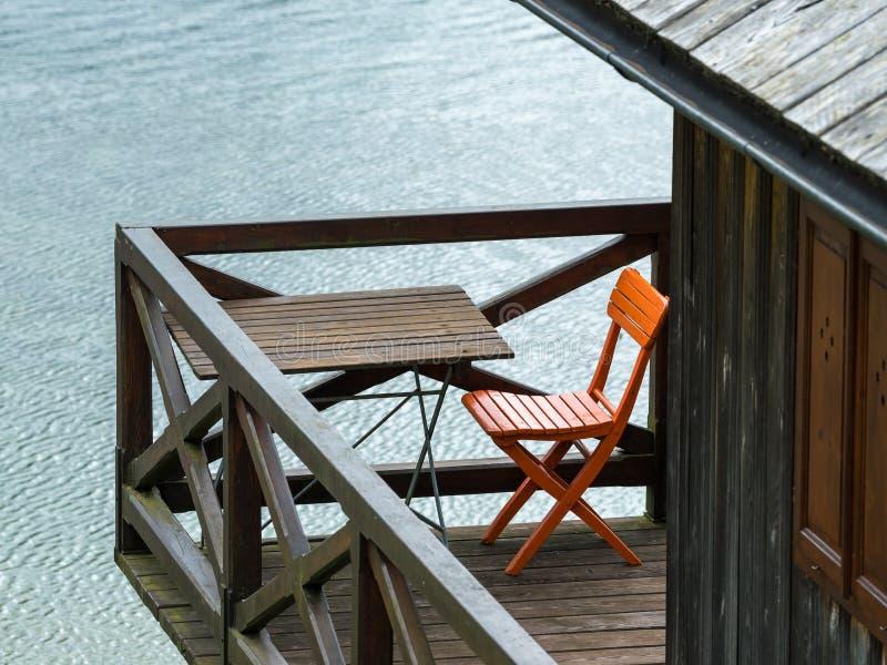Ein orange Stuhl und eine Tabelle, die auf einem Balkon stehen lizenzfreies stockbild