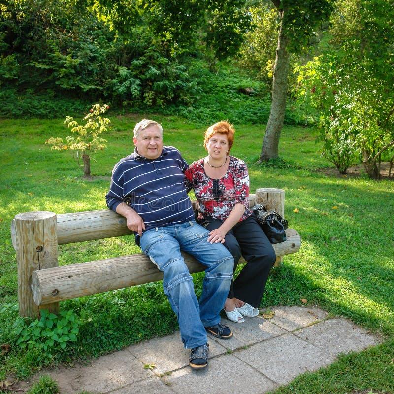 Ein paar ältere Menschen, die auf einer Bank stillstehen lizenzfreie stockbilder