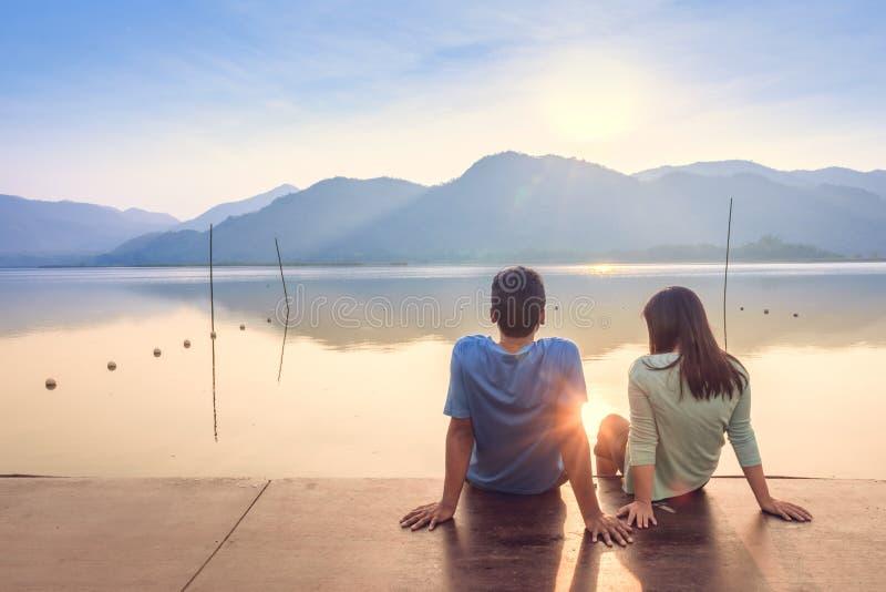 Ein Paar auf dem hölzernen Hafen an einem See auf Sonnenuntergang lizenzfreie stockfotografie