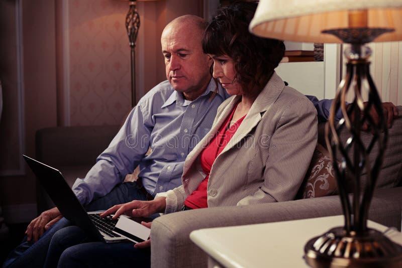Ein Paar auf dem Sofa mit Notizbuch im reizenden Raum lizenzfreie stockfotos