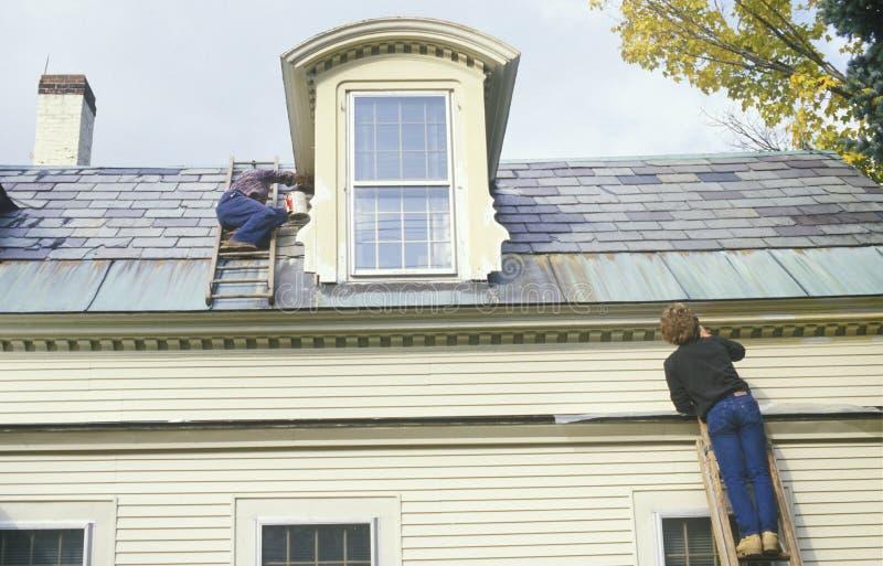 Ein Paar auf den Strichleitern, die ihr Haus malen stockfoto