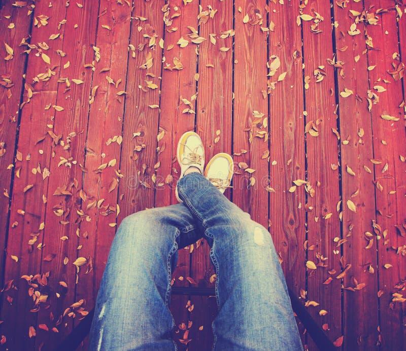 Ein Paar Beine genommen von den Unkosten auf einer Plattform mit Blättern die ha stockfoto