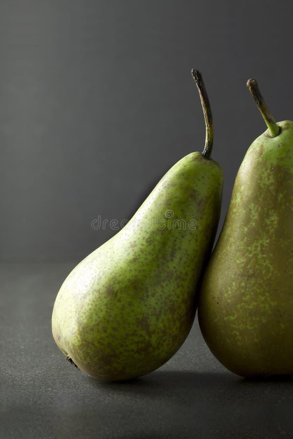 Ein Paar Birnen auf einem dunklen Hintergrund stockfotografie