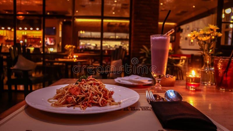 Ein Paar, das auf dem Tisch romantisches Kerzenlichtabendessen mit aglio Olio genießt lizenzfreie stockfotos
