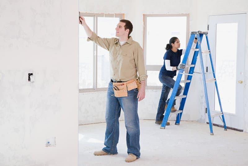 Ein Paar, das Gebäudearbeit erledigt lizenzfreies stockfoto