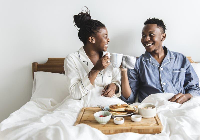 Ein Paar, das im Bett frühstückt stockfoto