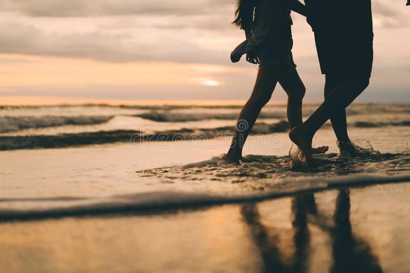 Ein Paar, das nahe dem aufpassenden Sonnenuntergang des Ozeans geht lizenzfreies stockbild