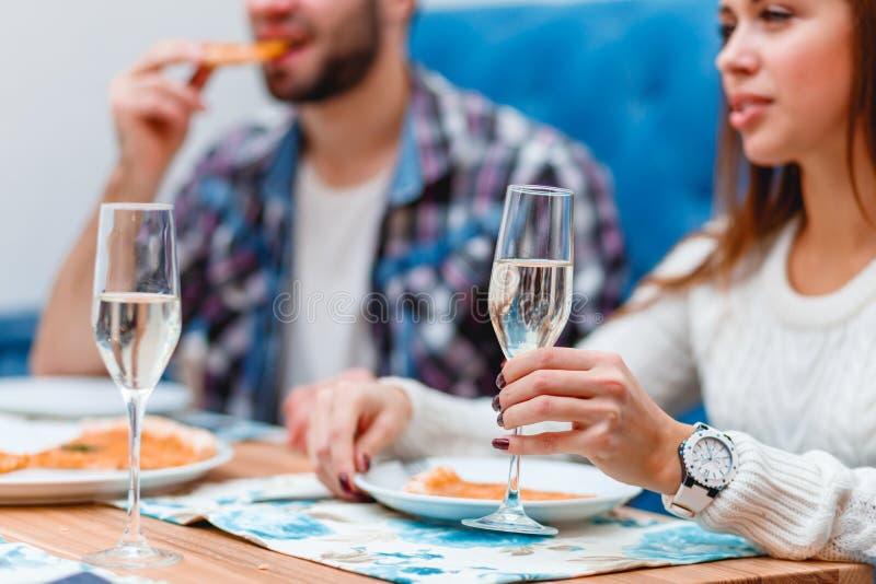 Ein Paar, das Zeit in einem Café isst eine Pizza und trinkt Champagner verbringt lizenzfreie stockfotografie