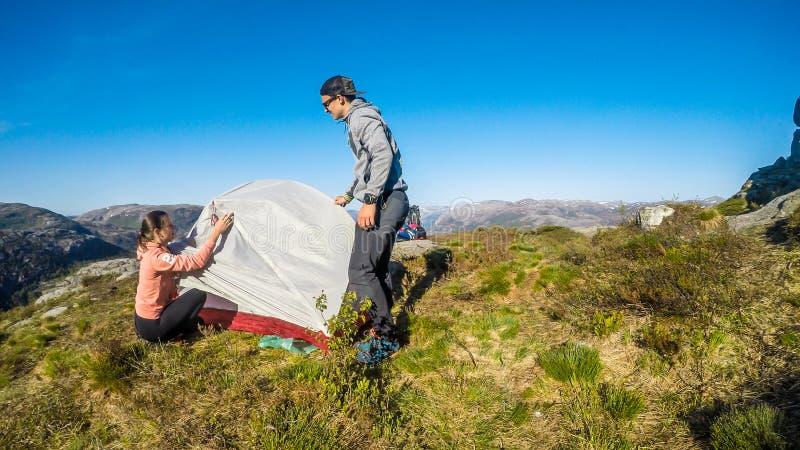 Ein Paar, das ein Zelt in der Wildnis in Norwegen aufbaut lizenzfreies stockfoto