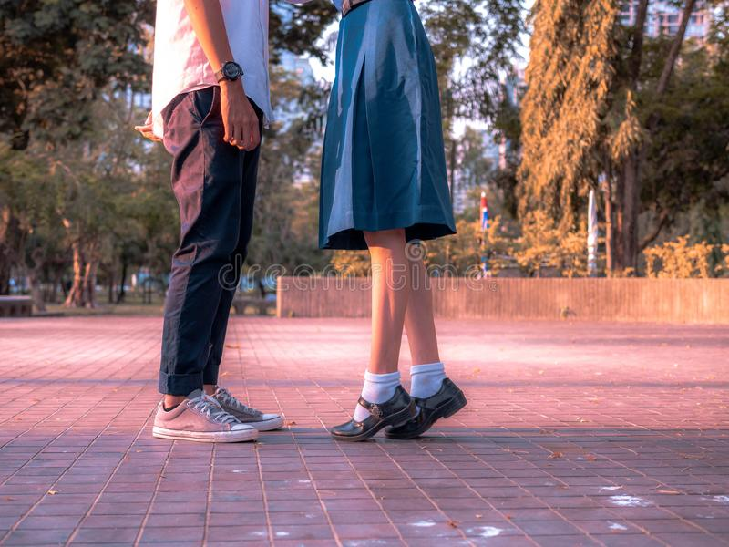 Ein Paar, das zusammen stehen, Beine und Turnschuhe von Paaren in der Schuluniform, die im Park, Symbolzeichen-Paarumfassung steh lizenzfreie stockfotos