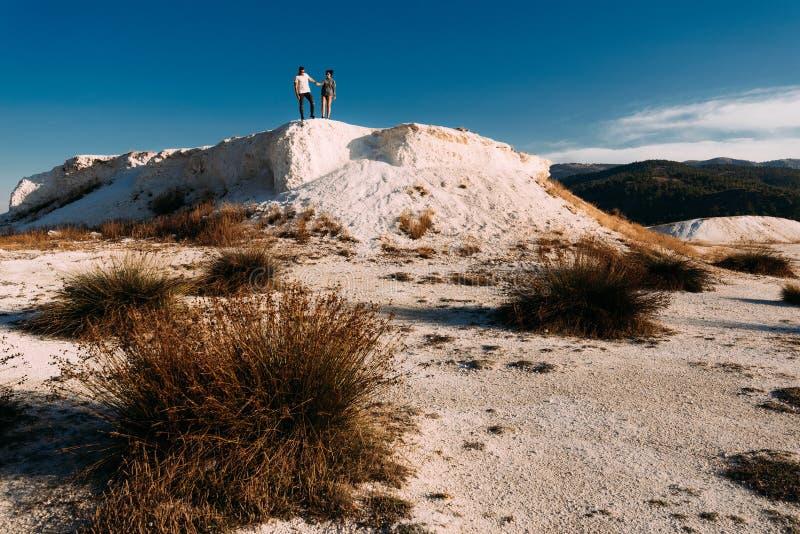 Ein Paar in der Liebe auf dem Hügel bewundert die schönen Ansichten Mann- und Frauenstellung auf dem Berg Ein Paar in den Liebesr lizenzfreies stockbild