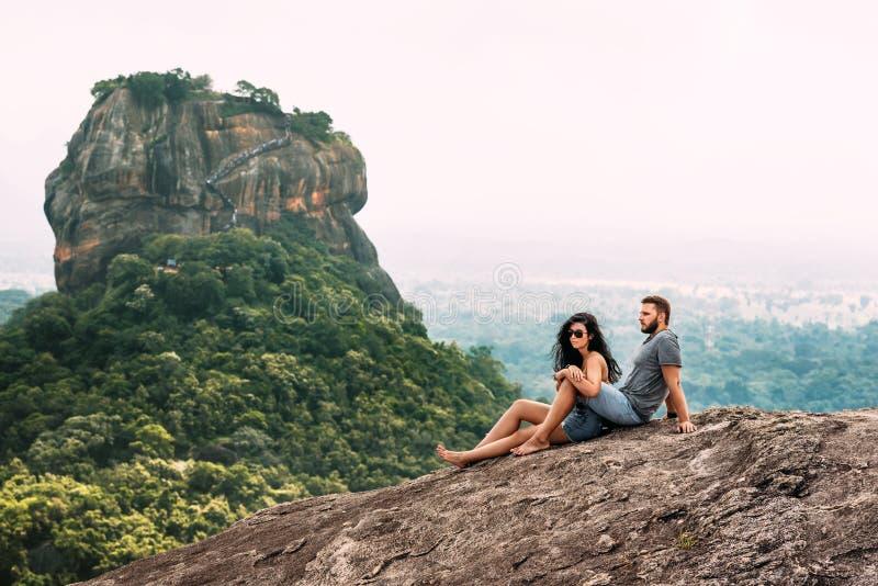 Ein Paar in der Liebe auf einem Felsen bewundert die sch?nen Ansichten Junge und M?dchen auf dem Felsen Ein Paar in den Liebesrei stockfotografie