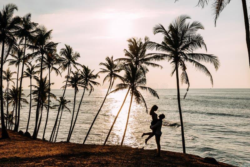Ein Paar in der Liebe trifft einen Sonnenuntergang auf dem Meer unter den Palmen Mann und Frau bei Sonnenuntergang Flitterwochen  stockfotos