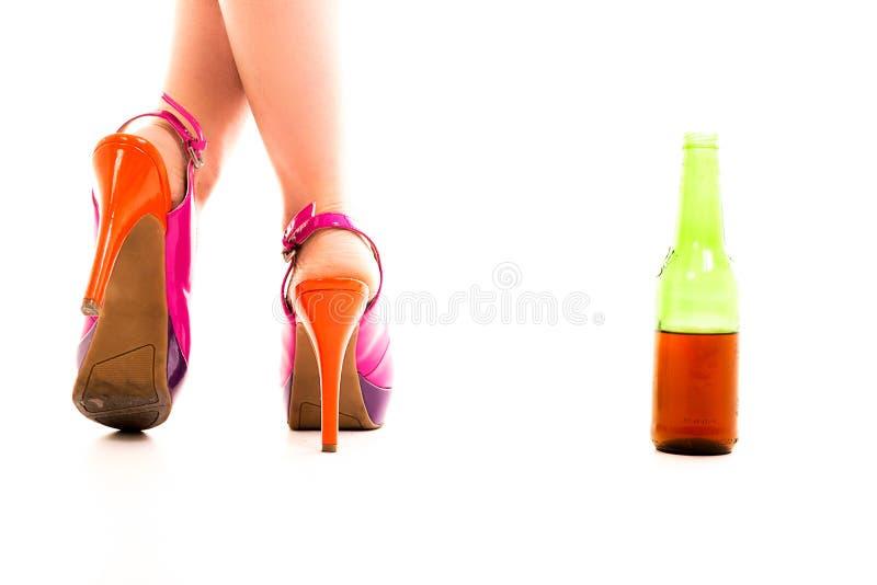 Ein Paar der roten Fersenschuhe und der Flasche Bieres stockfotos