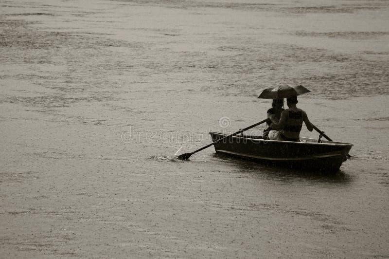 Ein Paar entgeht dem starken Regen auf einem Boot im Central Park in New York stockfotos