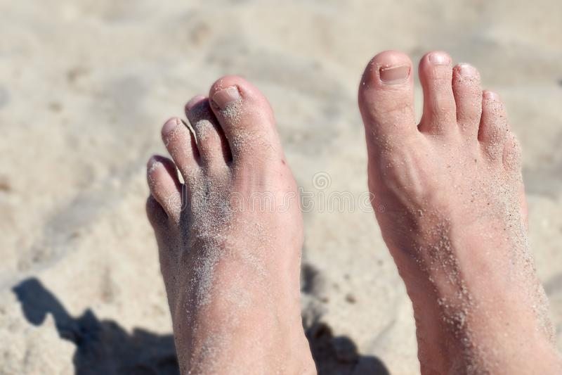 Ein Paar Füße im Sand lizenzfreie stockbilder