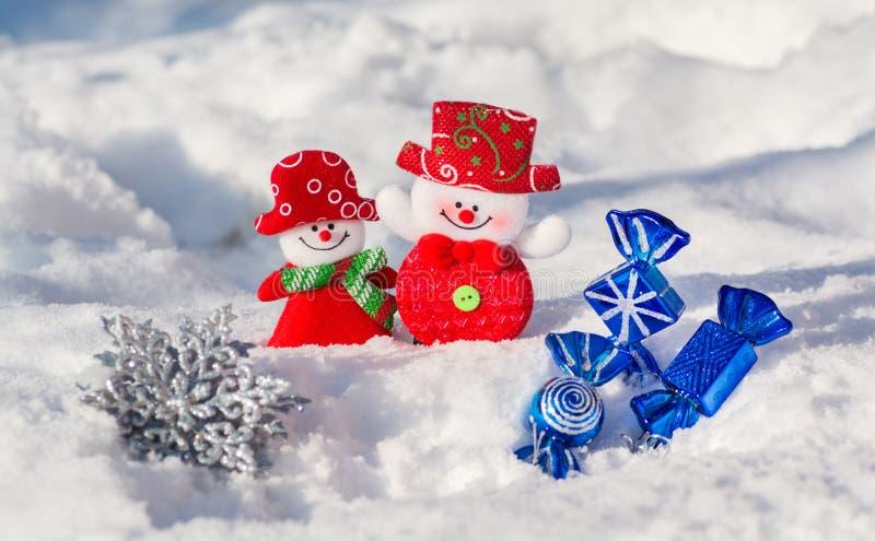 Ein Paar fröhliche Schneemänner im Schnee mit Weihnachten spielt mit blauen Süßigkeiten und einer silbrigen Schneeflocke Frohe We lizenzfreie stockfotos