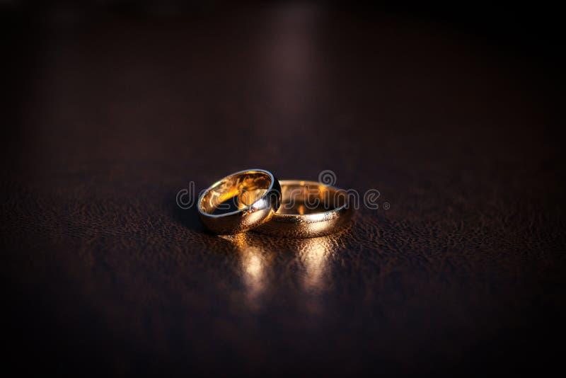 Ein Paar Goldeheringe, klassische Goldringe, auf einem dunklen Hintergrund stockfotografie