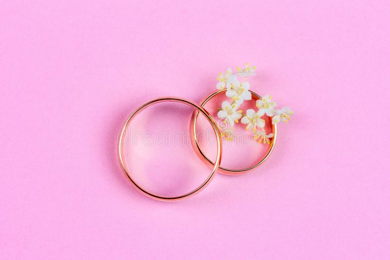 Ein Paar Goldeheringe und kleine weiße Blumen in einem Ring auf einem rosa Hintergrund, Draufsicht stockfotografie