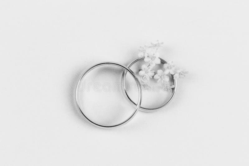 Ein Paar Goldeheringe und kleine weiße Blumen in einem Ring auf einem weißen Hintergrund stockbilder