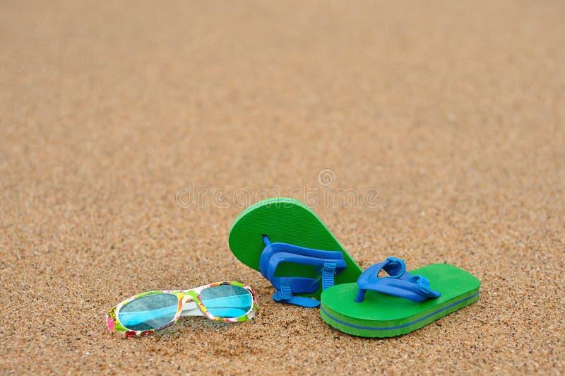 Ein Paar grüne und blaue Flipflops mit bunter Sonnenbrille lizenzfreies stockbild
