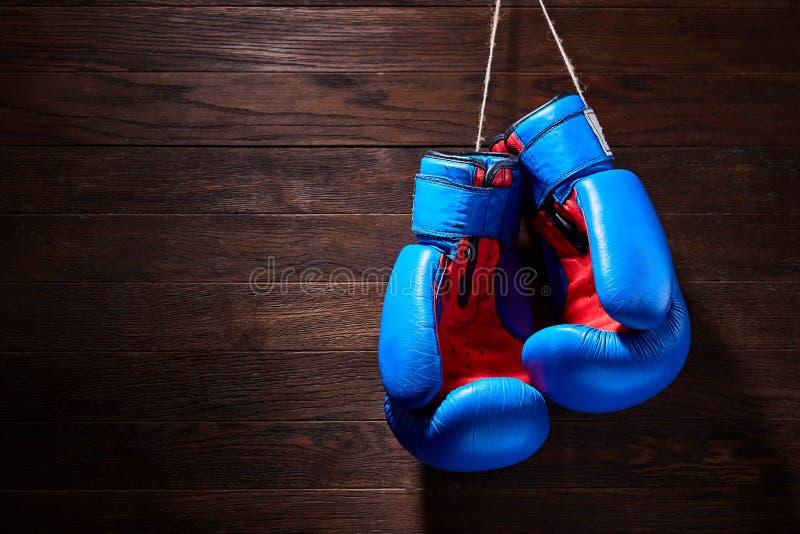 Ein Paar helle blaue und rote Boxhandschuhe hängt gegen hölzernen Hintergrund lizenzfreie stockfotografie