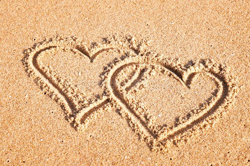 Ein Paar Herzen gemalt auf dem Sand im Sommer in dem Meer stockbild