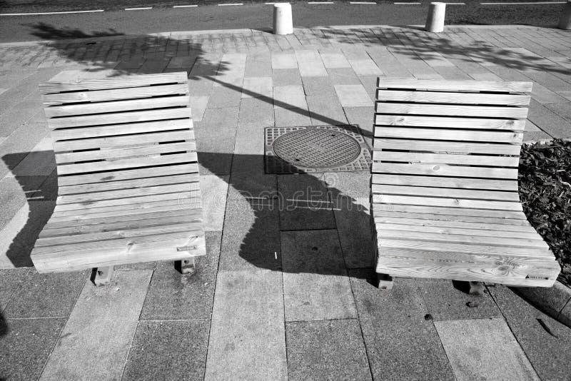 Ein Paar Holzbanken auf dem Bürgersteig mit lang einen in Schwarzweiss stockfoto