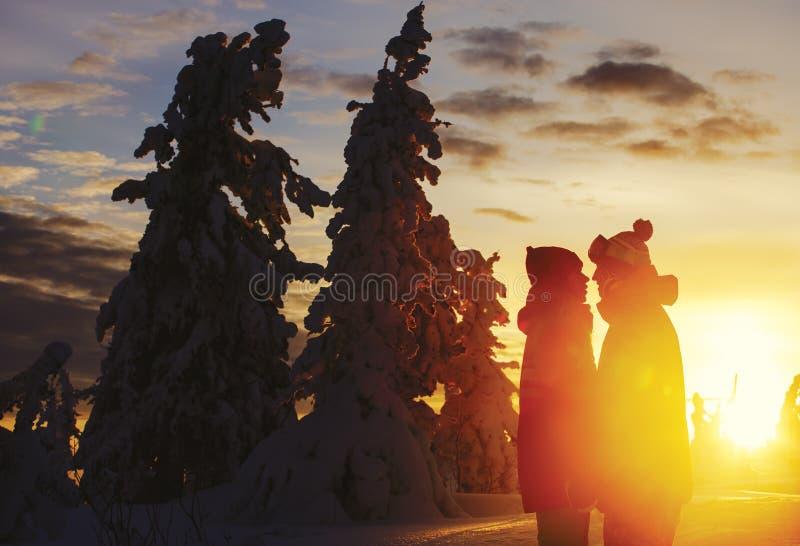 Ein paar junge Leute, ein Mann und ein Mädchen auf einem Berg auf einem Sonnenuntergang stockfotos