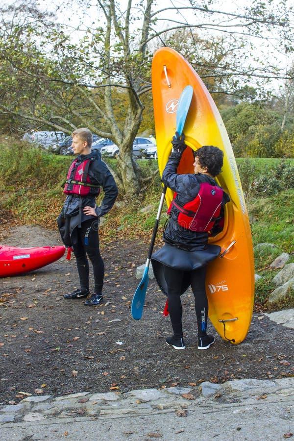 Ein paar junge Männer, die ihre Bootfahrtausrüstung nach einem Nachmittag des Kajaktrainings auf dem See in Castlewellan Forest P stockbilder