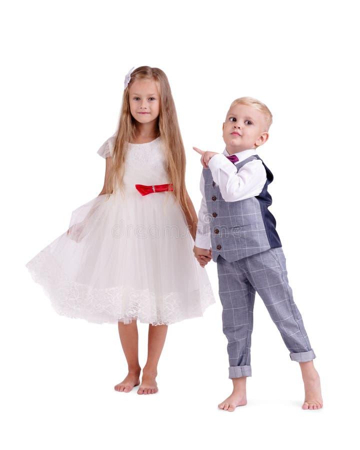 Ein paar kleine Freunde, welche die schöne Kleidung, lokalisiert auf einem weißen Hintergrund tragen Das Konzept von Valentinsgru lizenzfreies stockbild