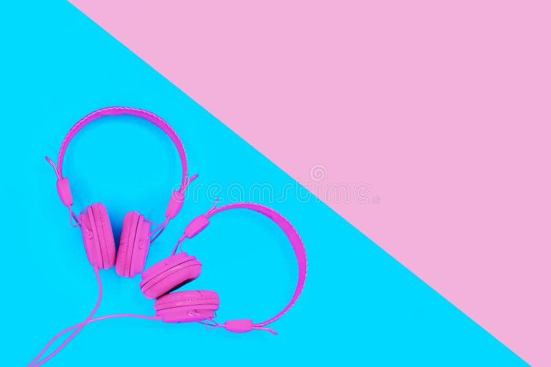 Ein Paar rosa Kopfhörer in Form eines Herzens auf blauem Hintergrund Sommerliebes-Musikkonzept mit Kopienraum stockfotografie