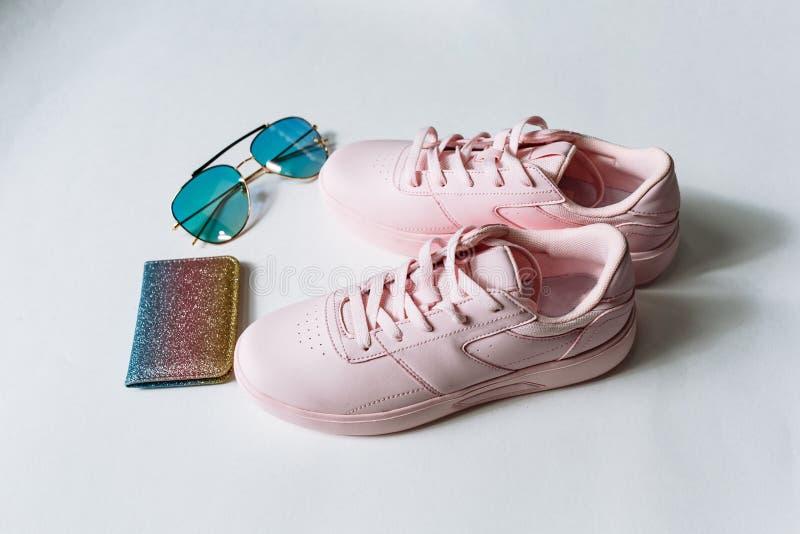 Ein Paar rosa lederne Turnschuhe, Geldbeutel mit mehrfarbigen Pailletten und Sonnenbrille mit blauem Glas auf einem wei?en Hinter lizenzfreies stockbild
