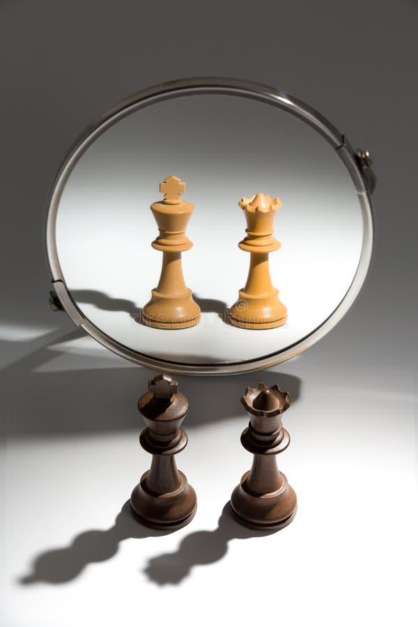 Ein paar schaut ein schwarzer König und eine Königin in einem Spiegel, um sich als weißes Paar zu sehen stockfoto