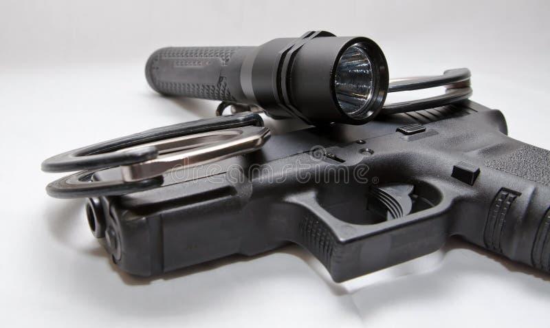 Ein Paar schwarze und silberne Handschellen mit einer schwarzen Taschenlampe, die auf eine schwarze halb automatische Pistole leg lizenzfreie stockfotos