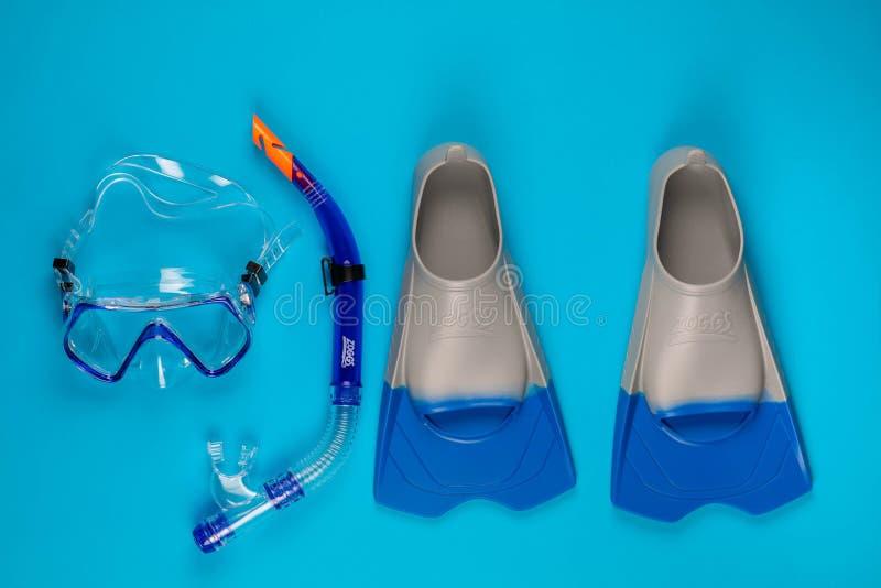 Ein Paar schwimmende Schutzbrillen nahe bei einem Paar Flossen, auf blauem Hintergrund lizenzfreie abbildung