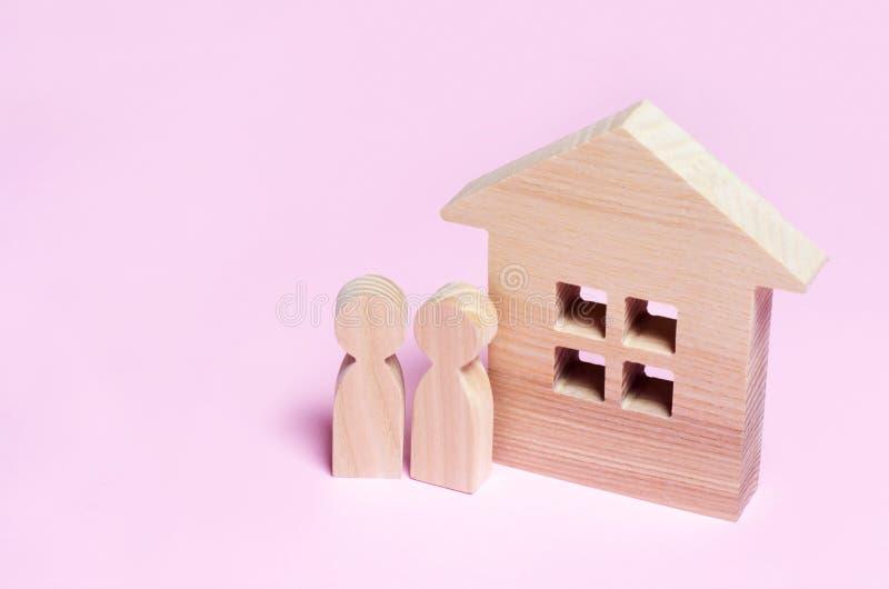 Ein Paar steht nahe einem Haus auf einem rosa Hintergrund Conc stockbilder