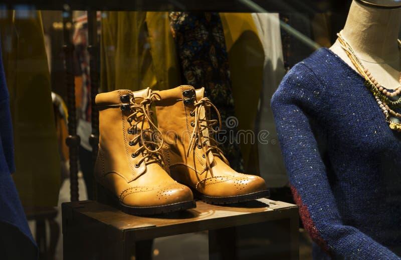 Ein Paar von Lederstiefeln und von weiblichen Mannequin in einem Modeshopfenster lizenzfreies stockbild