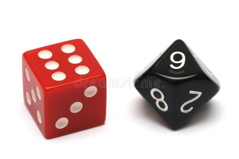 Ein Paar Würfel - man ist rotes sechs mit Seiten versehen, während das andere schwarze zehn mit Seiten versehen ist stockfotos