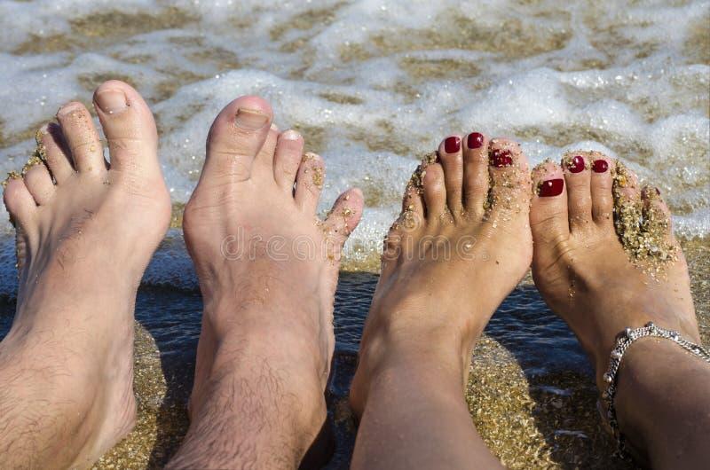 Ein Paare ` s Füße auf dem Hintergrund des Meeres stockbilder
