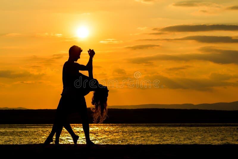 Ein Paartanzen durch das Meer bei Sonnenuntergang lizenzfreies stockfoto