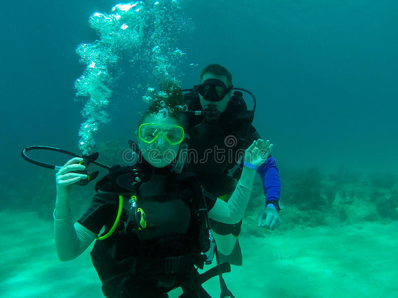 Ein Paarunterwasseratemgerättauchen zusammen Ein weiblicher Sporttaucher mit dem Regler heraus Lächeln, den Regler halten taucher stockbilder