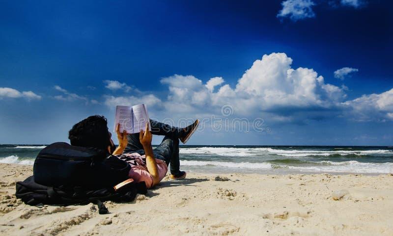 Ein palästinensisches Kind, das ein Buch auf dem Strand liest lizenzfreie stockfotografie