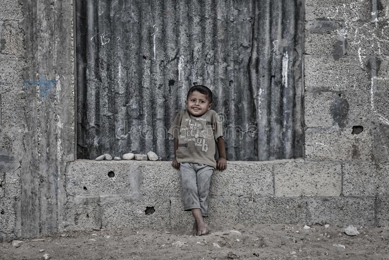 Ein palästinensisches Kind lächelt von den toten Nachbarschaften von Gaza-Stadt lizenzfreie stockbilder