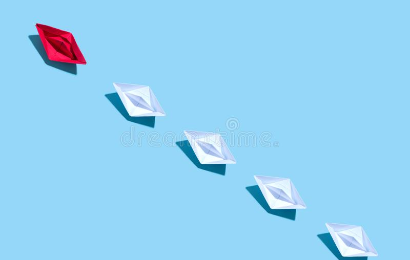 Ein Papierboot, das andere Boote führt stock abbildung