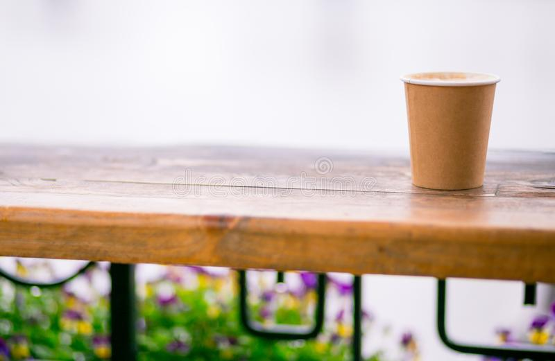 Ein Papiertasse kaffee mit Cappuccinoschaum-Kaffeekunst im Stra?enhintergrund Kraftpapierschale stockfotos