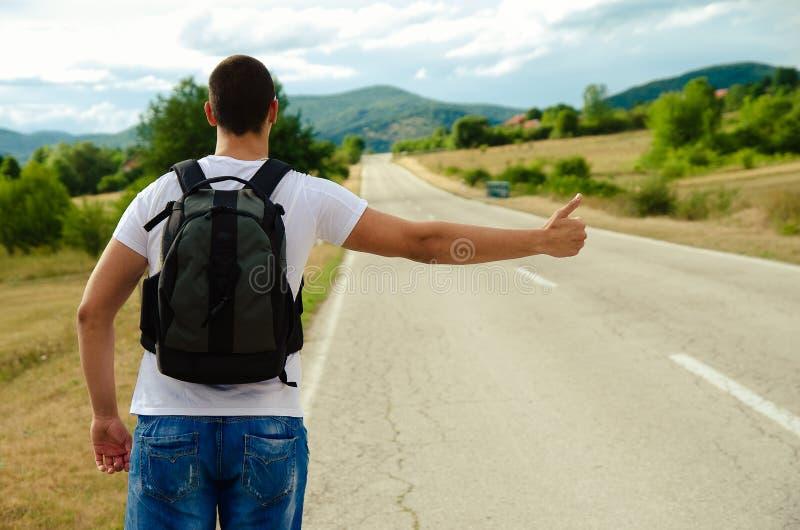 Ein Passagier mit einem Rucksack steht auf der Straße und stoppt stockfotografie