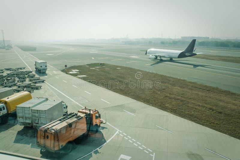 Ein Passagierflugzeug, das durch Grunddienstleistungen vor folgendem Start instand gehalten wird stockfotografie