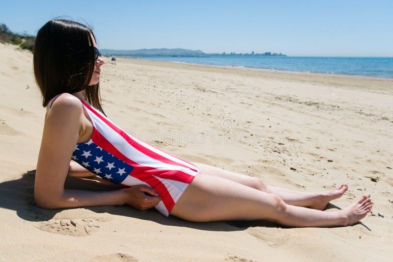Ein Patriot der jungen Frau liegt auf dem Strand in einem Badeanzug die Farben der US-Flagge stockbilder