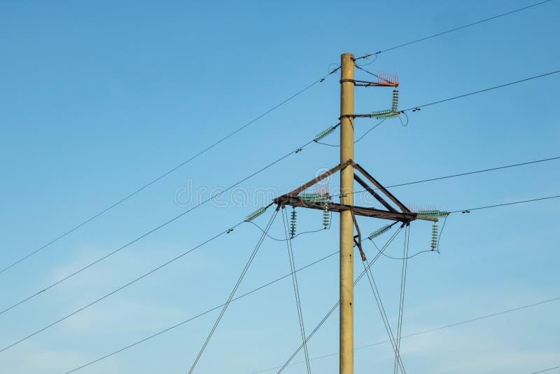 Ein Pfosten mit elektrischen Drähten gegen einen blauen Himmel stockfotos